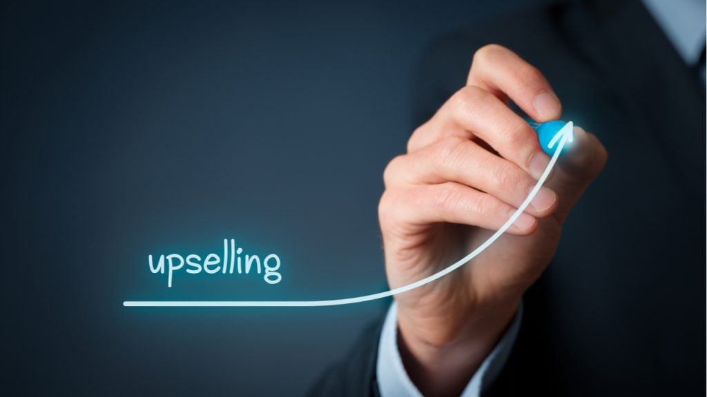 What does upselling in retail mean